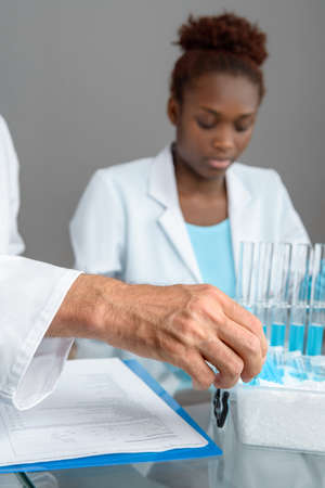 nitril: Closeup on a hand of a senior male scientist picking up scientific sample from ice box, working African female scientist out of focus, text space