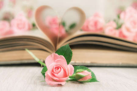 text pink: Pages of an old book curved into a heart shape and little pink roses on wooden table. Valentines day card.