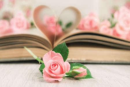 Pagina's van een oud boek gebogen in een hartvorm en kleine roze rozen op een houten tafel. Valentijnsdag kaart.