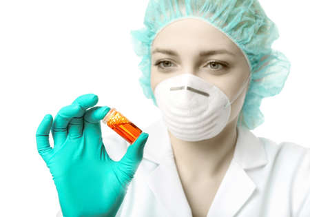lab tech: Female scientist or tech in lab coat, gloves and hat holds liquid biological sample. This image is isolated on white. Shallow DOF, focus on the tube and hand. This image is toned.