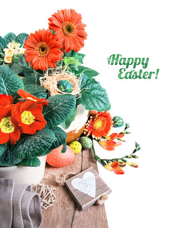 herbera: Easter border with orange herbera, freesias and spring decorations, caption Happy Easter! on plain white background, space for your text. This image is toned. Stock Photo