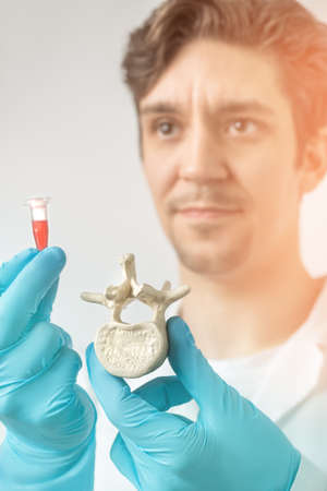 vertebra: Doctor or scientist holds vertebra and a tube with red liquid in gloved hands. Shallow DOF, focus on the bone. This image is toned.