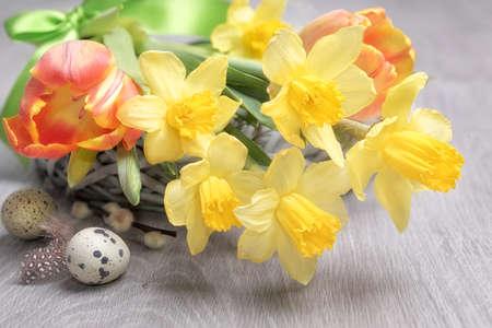 composizione floreale di Pasqua con narcisi gialli, tulipani arancioni e uova di quaglia