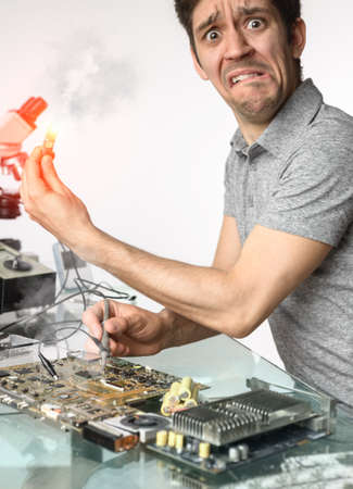 faulty: Distressed young male tech failing to fix faulty motherboard Stock Photo