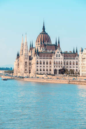 unrecognizable people: Parliament building in Budapest, Hungary, on a bright day across Danube, with unrecognizable people on the riverbank. This image is toned Stock Photo