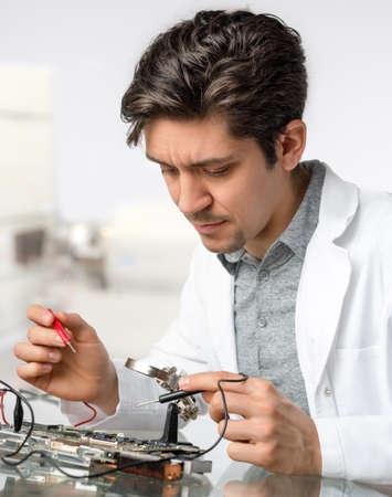 circuitos electronicos: Tecnología o ingeniero reparaciones masculinos energéticos joven equipo electrónico en el centro de investigación. Shallow DOF, se centran en la cara del trabajador.