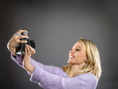 Attractive young woman in pale pink sweater with vintage portable camera on neutral dark background, space for your text
