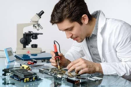 Jonge energieke mannelijke tech of ingenieur reparatie elektronische apparatuur in onderzoeksfaciliteit. Ondiepe DOF, focus op het gezicht en de handen van de werknemer.