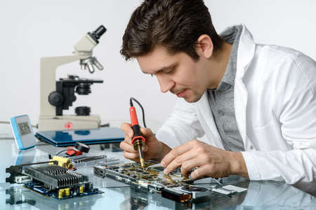 Young energetic male tech or engineer repairs electronic equipment in research facility. Shallow DOF, focus on the face and hands of the worker.