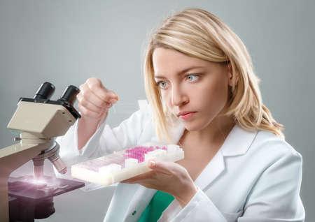 bata blanca: microscopista de sexo femenino joven en la capa blanca selecciona una muestra de tejido para el análisis microscópico