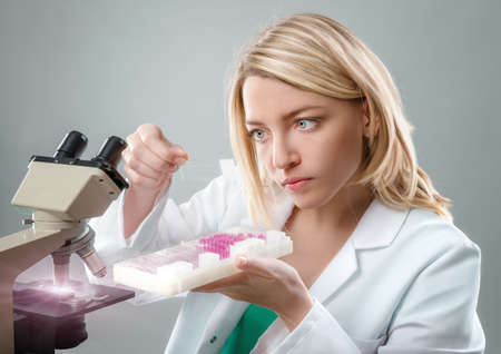 pathologist: Young female microscopist in white coat selects a tissue sample for microscopic analysis