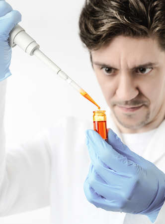 keen: Keen scientist with brown eyes in protective wear pipettes orange sample, Shallow DOF, focus on the pipette, drop, tube and gloved hand. This image is toned.