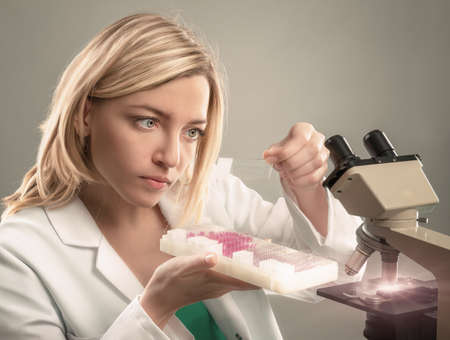 pathologist: Young female microscopist in white coat selects a tissue sample for microscopic analysis. This image is toned.