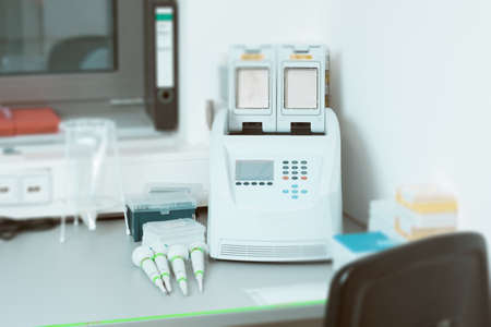 medical testing: Part of modern scientific laboratory with PCR machine for DNA amplification on work bench.