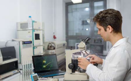 histology: Male scientist or tech with dark hair and brown eyes works with microscope samples in research facility