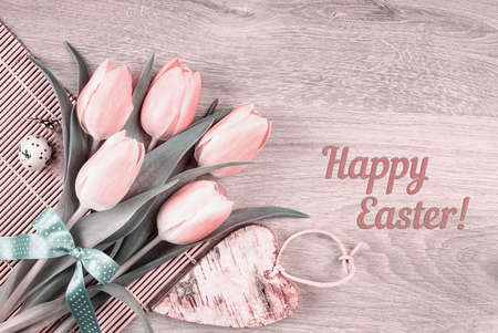 Easter card or webpage design. Bunch of pink tulips, quail egg and wooden heart on table, caption
