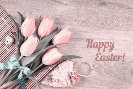 """huevo blanco: Tarjeta de Pascua o el diseño de páginas web. Ramo de tulipanes de color rosa, huevo de codorniz y corazón de madera en la tabla, el título """"Feliz Pascua!"""""""