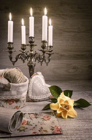 Still life with yellow rose, stuffed heart and vintage candlestick. This image is toned.