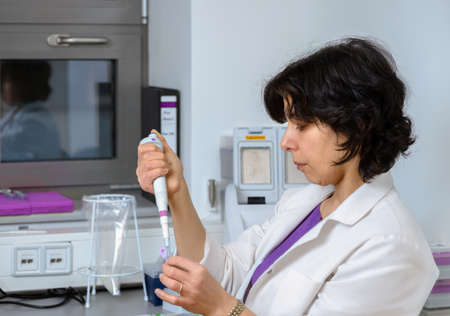 Senior scientist works with automatic pipette, toned image