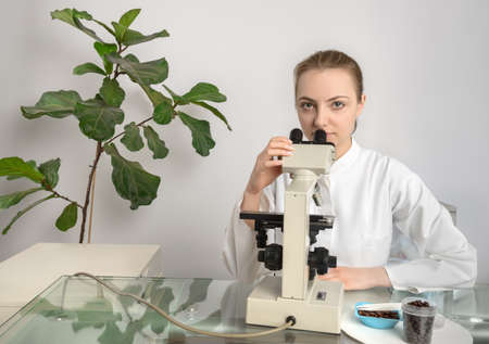 biologist: Young biologist or tech tests quality of coffee beans in research facility