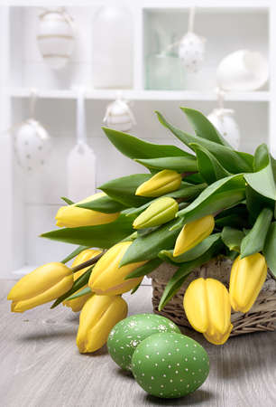 yelow: Yelow tulips, Easter eggs and decorations in a white shadowcase, space for your text