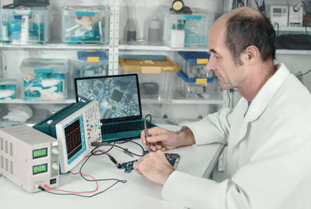Senior male tech is working in hardware repair facility