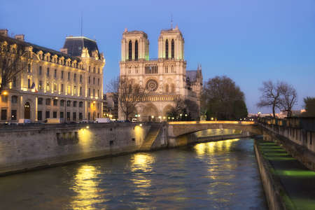 round window: Illuminated Notre Dame de Paris Cathedral and Seine River at night. Focus on the round window of the cathedral.