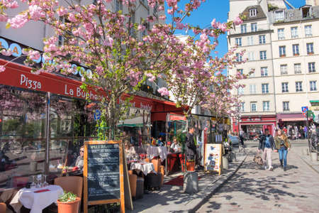 europeans: PARIS, FRANCE - APRIL 18 2016: A row of restaurants in Latin Quarter at Spring. Once a student neighbourhood, now the district is one of the most popular among tourists and locals alike.