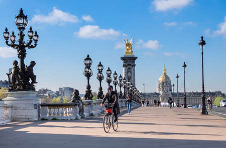 alexander: PARIS, FRANCE - APRIL 19 2016: Early morning pedestrians and cyclists on Alexandre Bridge in Paris on a bright sunny morning in Spring. Editorial