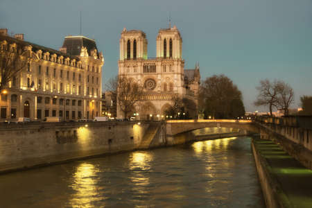 bell tower: Illuminated Notre Dame de Paris Cathedral and Seine River at night. Focus on the round window of the cathedral. This image is toned.