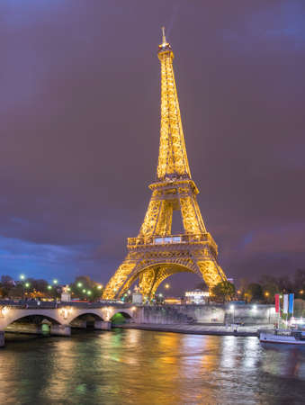 located: PARIS, FRANCE - APRIL 21 2016: The Eiffel tower at night. The Eiffel tower is a famous monument located on the bank of the Seine river in Paris, France.