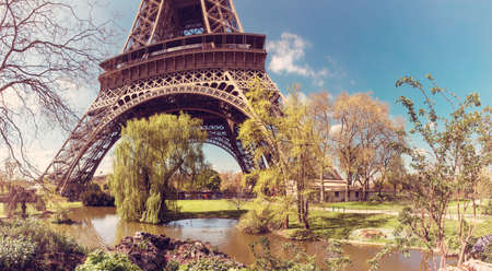 romance sky: Beatiful garden in spring with decorative lake at the feet of Eiffel Tower in Paris. Panorama image, toned for retro look Stock Photo