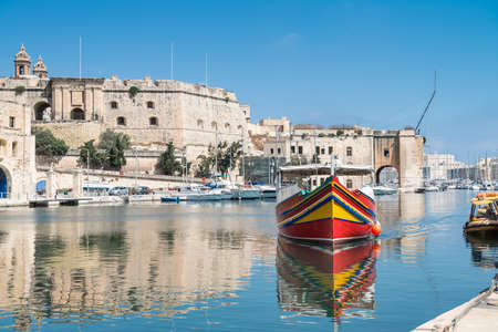 blue sea: Traditionally painted passenger boat transports passengers between Valetta and Vittoriosa in Grand Valetta Bay in Malta