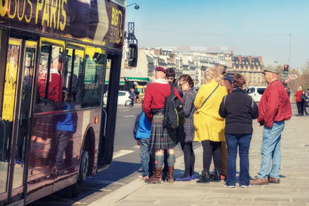 guide: PARIS, FRANCE - APRIL 20, 2016: Tourists board sightseeing bus in Paris City Senter. Paris is one of the most visited cities in the world. This image is toned. Editorial