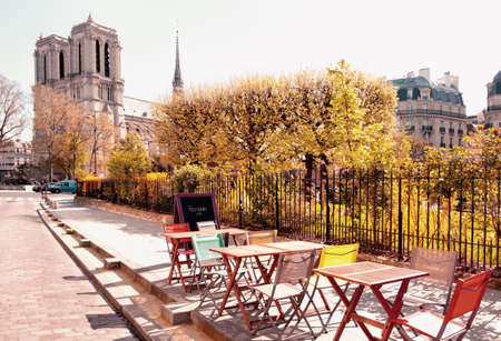 Autumn in Paris, tables and chairs of an outddoor cafe next to Notre Dame Cathedral. This image is toned.