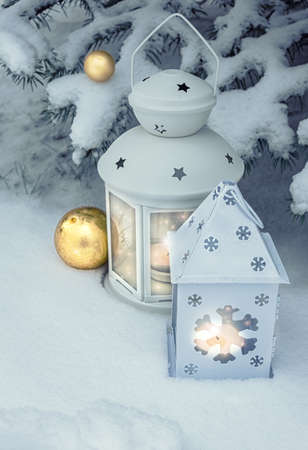 christmas candles: Little winter lanterns outdoors on a Christmas tree under snow. Merry Christmas!