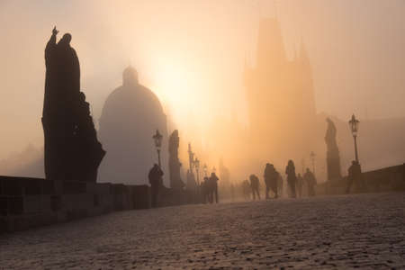 spectators: Spectators watch the dense fog on Charles Bridge on the bright Easter moring, as the Sun rises over the towers.
