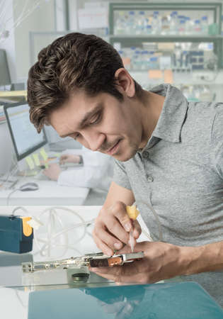 vaccuum: Young male tech with curly brown hair works in in research facility Stock Photo