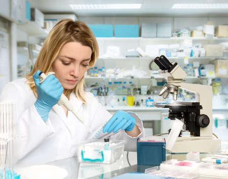 assay: Young female tech or scientist loads liquid sample into test tube with plastic pipette. Shallow DOF, focus on the eyelashes and hand with the tubes. Stock Photo