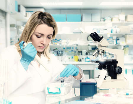 Young female tech or scientist loads liquid sample into test tube with plastic pipette. Shallow DOF, focus on the eyelashes and hand with the tubes. This image is toned. Stock Photo
