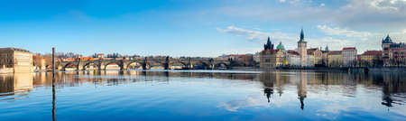 praha: Prague, Charles bridge reflected in Vltava river in the morning, panorama image