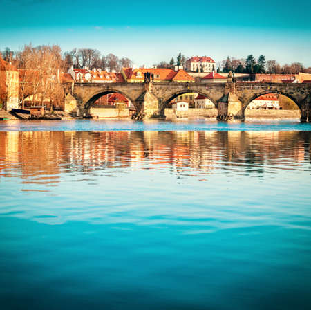 Prague, closeup on Charles bridge reflected in Vltava river in the morning, vertical panorama, space for text. This image is toned.