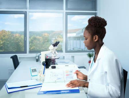 scienziato, studente laureato africana o coordinatore sperimentazione medica lavora nel suo ufficio