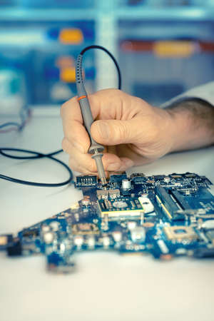 hardware repair: Closeup on electronic board in hardware repair shop. Shallow DOF, focus on the hand and tester tool, space for your text. This image is toned. Stock Photo
