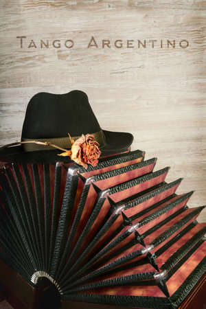 milonga: Bandoneon on wooden background with a male black hat on top, burnt caption Tango Argentino