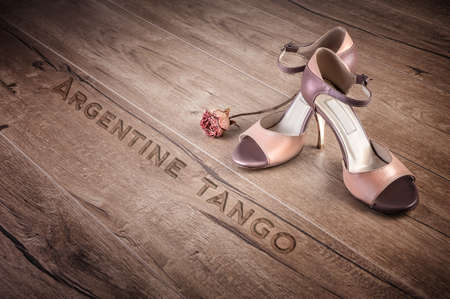 Argentine tango shoes and a dry rose on a wooden floor, caption