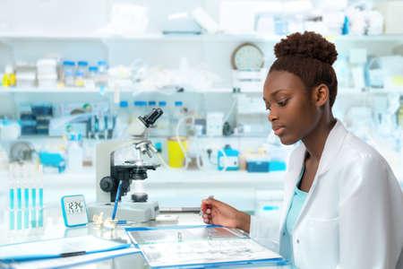 Afrykański naukowiec, pracownik medyczny, technika lub student pracuje w nowoczesnym laboratorium biologicznym