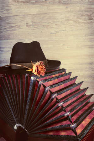 bandoneon: Bandoneon on wooden background with a male black hat on top, text space. This image is toned. Stock Photo