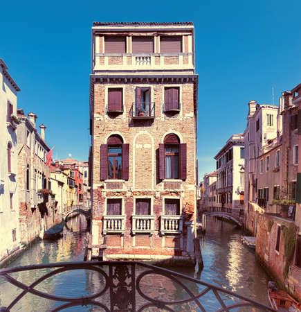 waterways: Old houses and waterways in central Venice in Italy on a bright day. This image is toned. Stock Photo