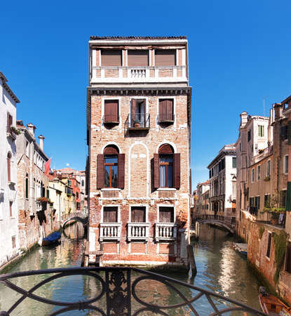 ochre: Old houses and waterways in central Venice in Italy on a bright day